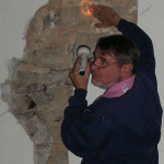 Walter Brosz explains mortar evidence of original log cabin loft abutting stone west wing