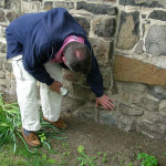 Walter Brosz shows proof of west stone wing lapping original log cabin